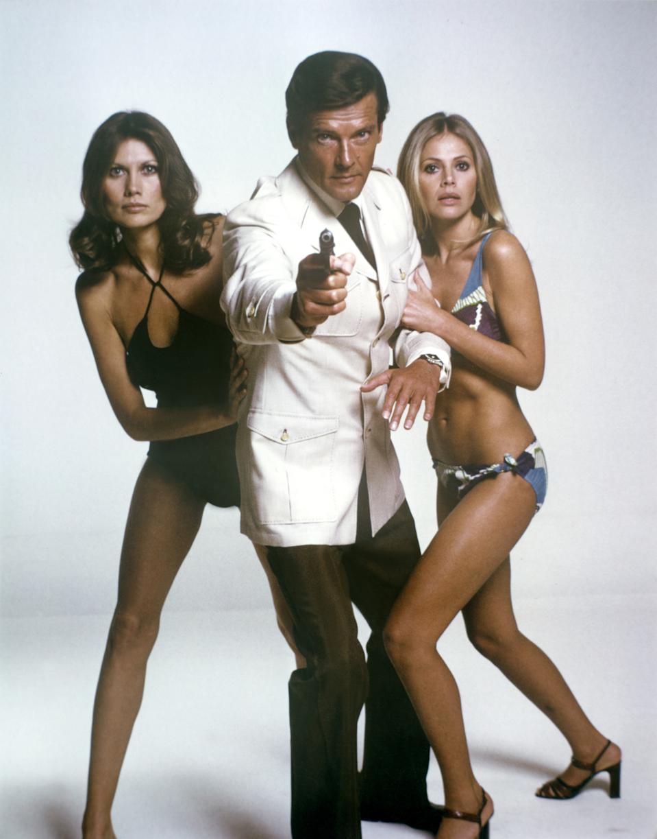 """Actor Roger Moore with actresses Maud Adams and Britt Ekland on the set of """"The Man With The Golden Gun"""". (Photo by Sunset Boulevard/Corbis via Getty Images)"""