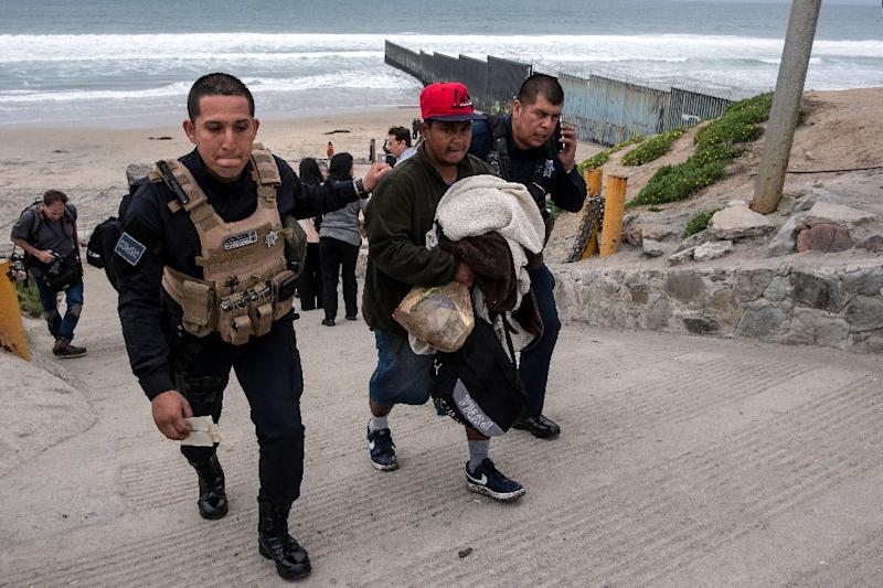 A Central American man is taken into custody by Tijuana police (AFP Photo/Guillermo Arias)