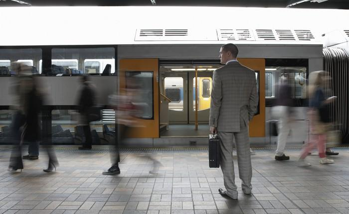 Man in suit on train platform in front of a train with open doors