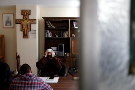 Venezuelan priest Luis Antonio Salazar and a camera operator, prepare a script for a video for his social media at his office at Chiquinquira Catholic church in Caracas