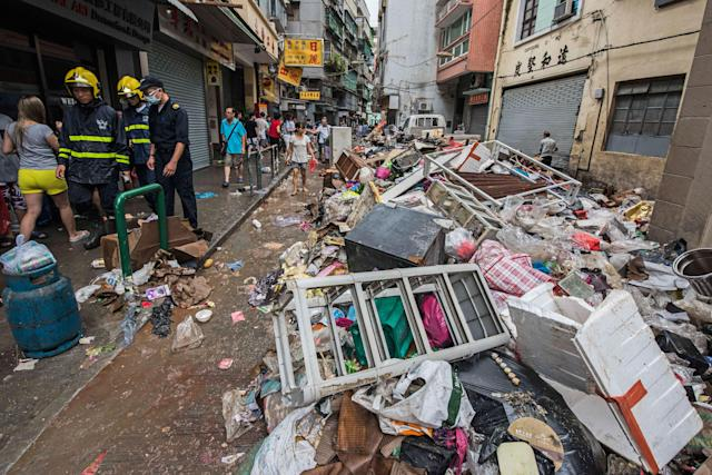 <p>Firefighters and pedestrian pass by debris after the passage of Typhoon Hato in Macau, China, Aug. 23, 2017. (Photo: Antonio Mil-Homens/EPA/REX/Shutterstock) </p>