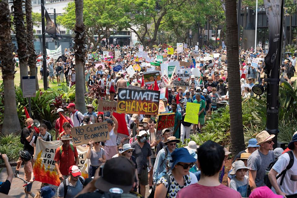Demonstrators hold up placards during a climate protest rally in Sydney on December 21, 2019. - Hundreds of protesters gathered at First Fleet Park and marched onto the Sydney Harbour Bridge on November 21, demanding urgent climate action from Australia's government, as bushfire smoke choking the city caused health problems to spike. (Photo by Wendell TEODORO / ZEDUCE / AFP) (Photo by WENDELL TEODORO/ZEDUCE/AFP via Getty Images)