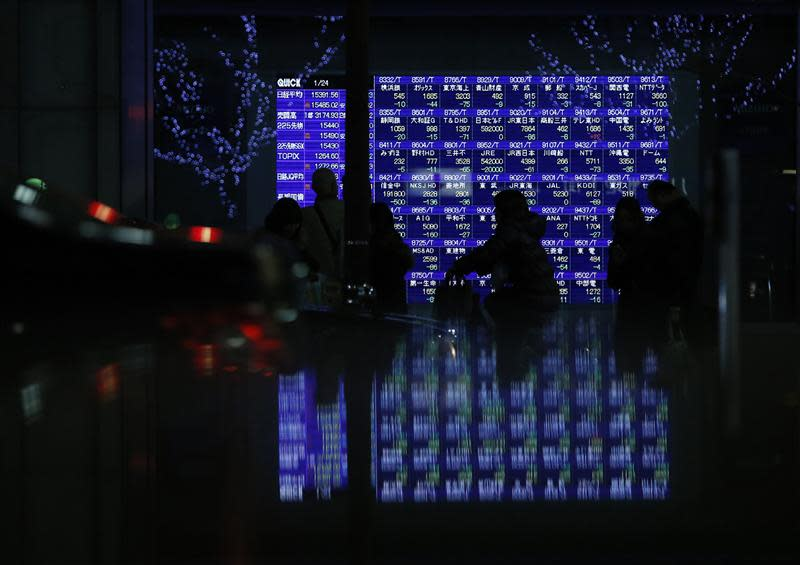 Pedestrians walk past an electronic board showing various stock prices outside a brokerage in Tokyo