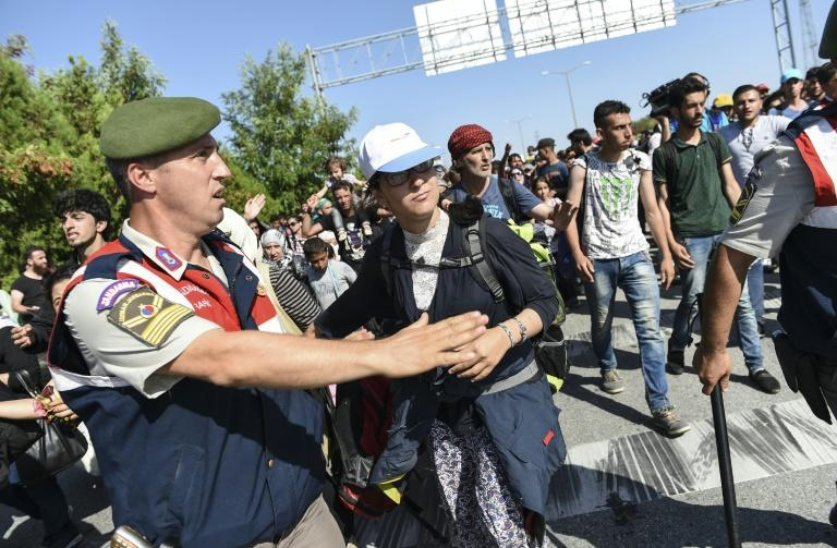 A Turkish police officer gestures to colleagues as Syrian migrants and refugees march along the highway towards the Turkish-Greek border at Edirne on September 18, 2015