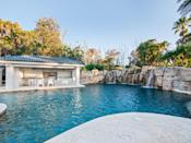 <p>The 95-foot-long, 15-feet-deep pool is surrounded by a gorgeous rock waterfall, as well as a hot tub, expansive summer kitchen, and more.</p>