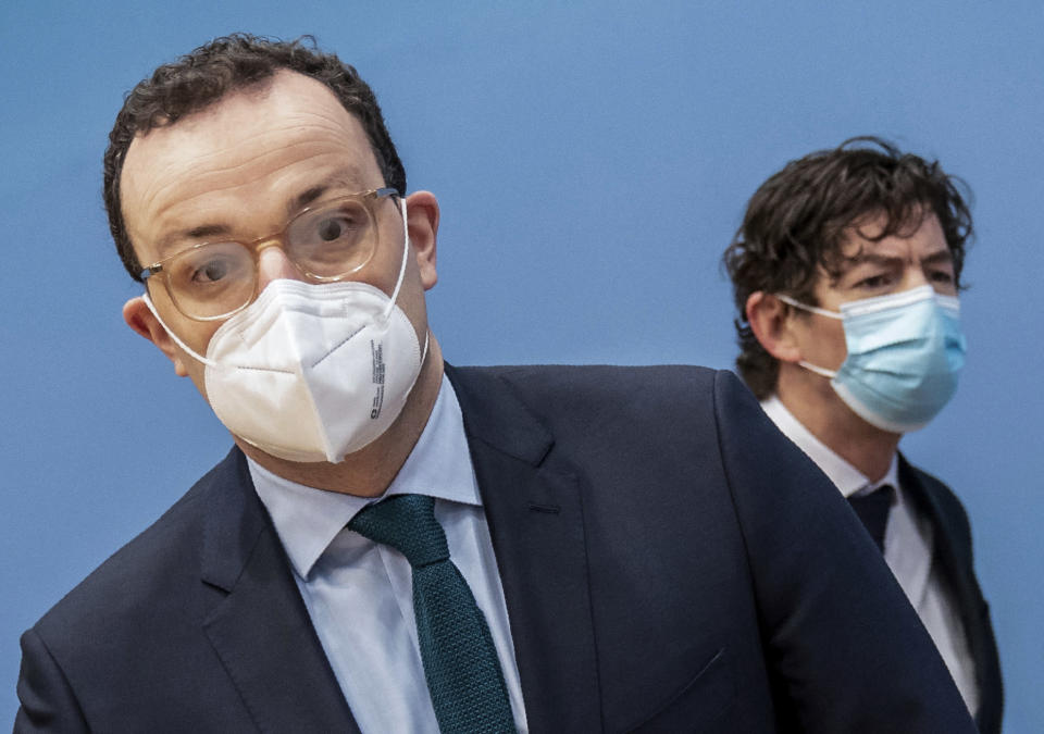 Jens Spahn, left, Federal Minister of Health, and Christian Drosten, Director of the Institute of Virology, Charité Berlin, arrive for a press conference on the current situation in the Corona pandemic in Berlin, Germany, Friday, Jan.22, 2021. (Michael Kappeler/dpa Pool via AP)