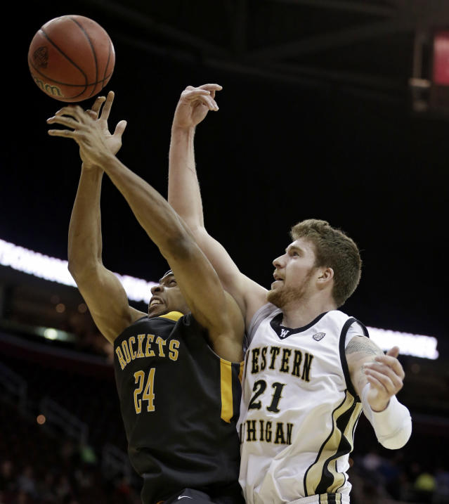 Toledo's J.D. Weatherspoon (24) and Western Michigan's Shayne Whittington (21) battle for a rebound during the first half of an NCAA college basketball championship game at the Mid-American Conference tournament on Saturday, March 15, 2014, in Cleveland. (AP Photo/Tony Dejak)