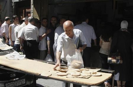 Syrians wait in line to buy bread at al-Shaalan market in Damascus