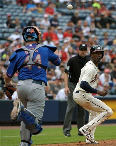 Atlanta Braves' B.J. Upton, right, is caught in a rundown by New York Mets catcher John Buck (44) during the fifth inning of a baseball game at Turner Field, Sunday, May 5, 2013, in Atlanta. (AP Photo/David Tulis)