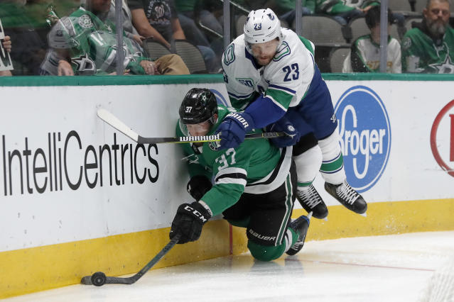 Dallas Stars center Justin Dowling (37) and Vancouver Canucks defenseman Alexander Edler (23) slam against the boards chasing a loose puck in the first period of an NHL hockey game in Dallas, Tuesday, Nov. 19, 2019. (AP Photo/Tony Gutierrez)
