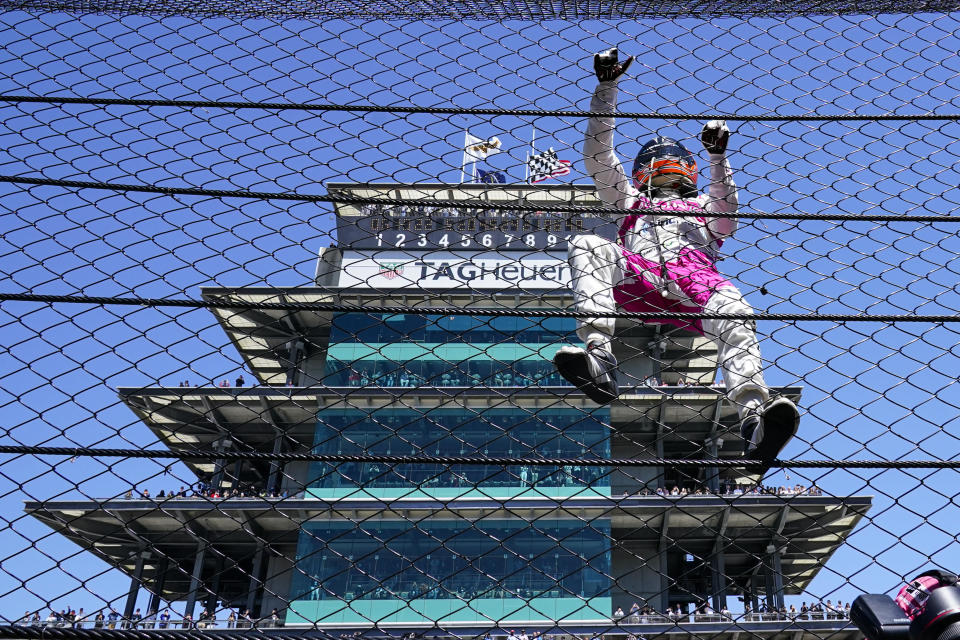 Helio Castroneves of Brazil climbs the fence at the start/finishing as he celebrates after winning the Indianapolis 500 auto race at Indianapolis Motor Speedway in Indianapolis, Monday, May 31, 2021. (AP Photo/Paul Sancya)