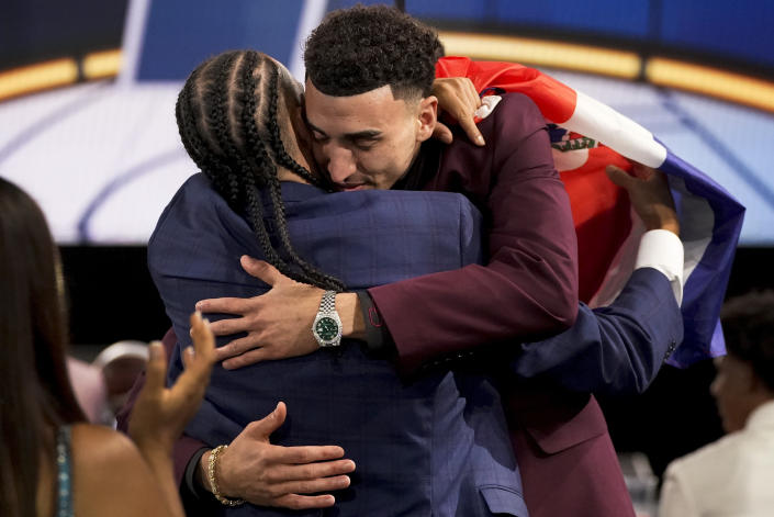 Chris Duarte, right, hugs supporters after being selected as the 13th overall pick by the Indiana Pacers during the NBA basketball draft, Thursday, July 29, 2021, in New York. (AP Photo/Corey Sipkin)