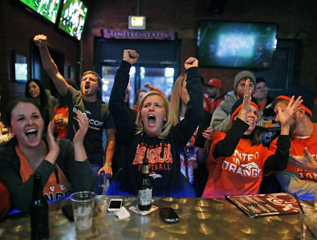 Liz Rogers, center, and her friend Caitlin O'Connor, left, celebrate as the Broncos complete a pass, while watching the first half of the Super Bowl against the Seahawks inside Jackson's, a sports bar and grill in Denver, Sunday, Feb. 2, 2014. (AP Photo/Brennan Linsley)
