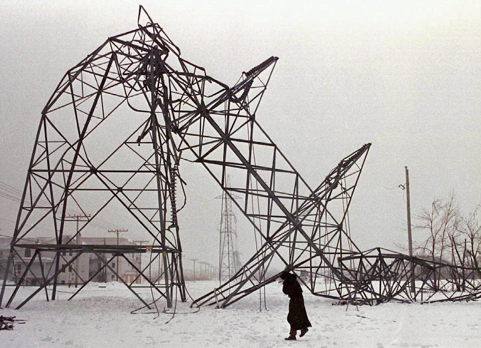 A transmission tower crumpled under the weight of ice