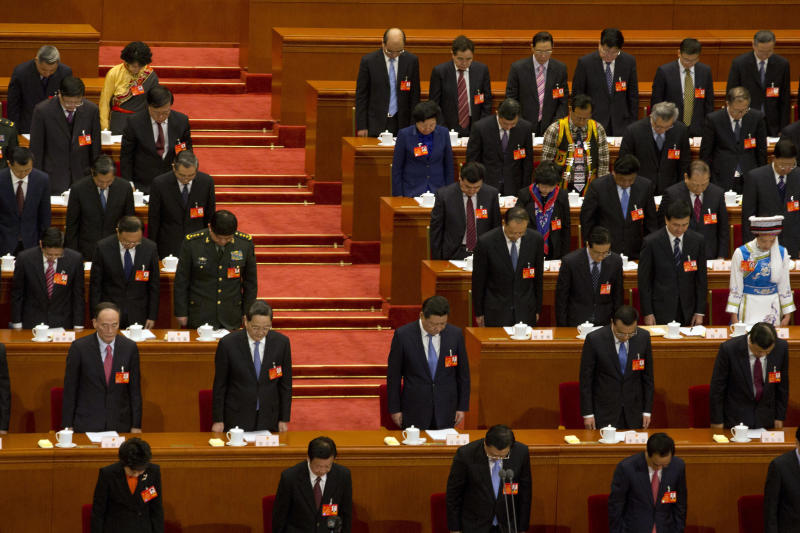 China's top leaders including Chinese President Xi Jinping, center, bow their heads to observe a minute of silence to commemorate the victims of the recent slashing incident in Kunming province during the opening session of the annual National People's Congress in Beijing's Great Hall of the People, China, Wednesday, March 5, 2014. (AP Photo/Ng Han Guan)