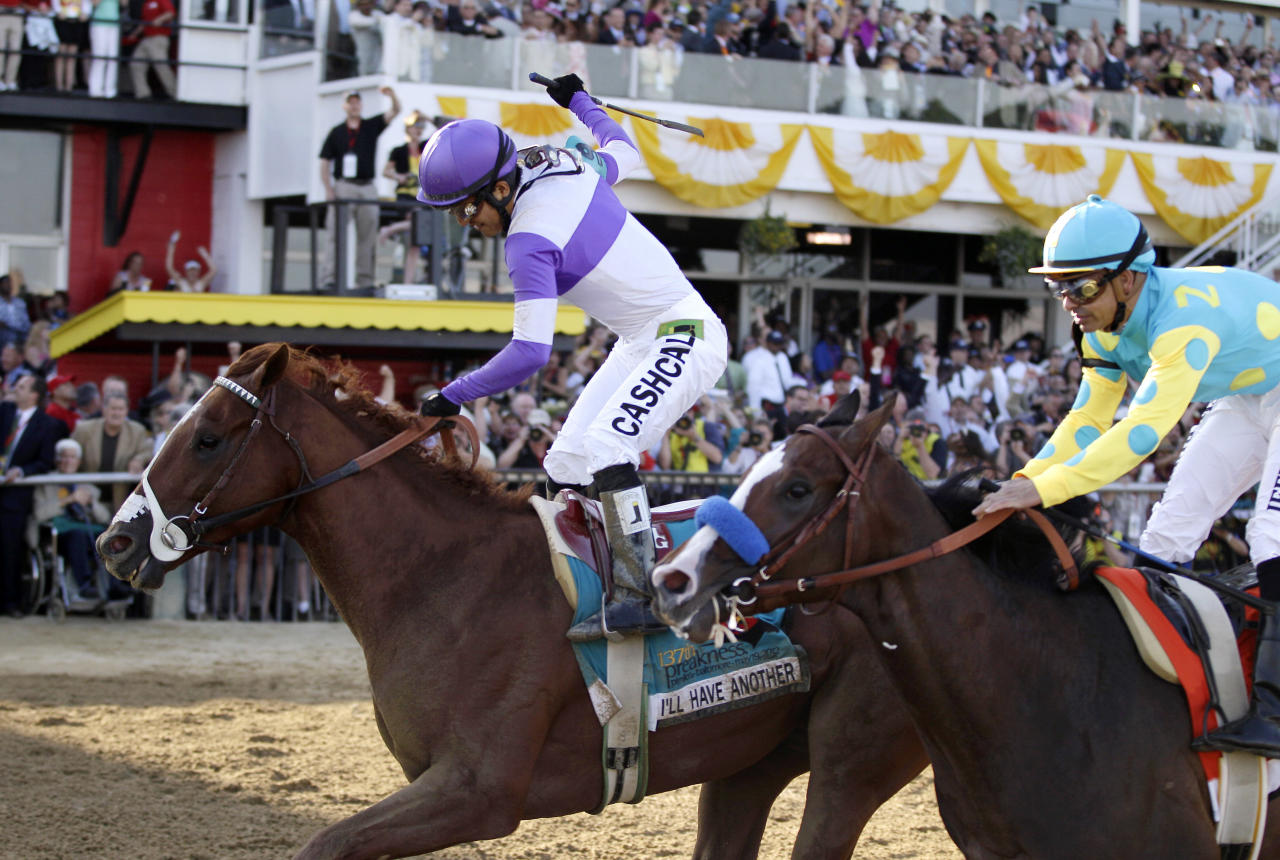 Jockey Mario Gutierrez, left, aboard, I'll Have Another, reacts after crossing the finish line in front of Bodemeister, right, ridden by Mike E. Smith, to win the 137th Preakness Stakes horse race at Pimlico Race Course, Saturday, May 19, 2012, in Baltimore. (AP Photo/Matt Slocum)