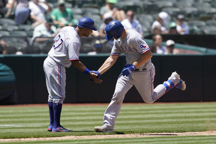 Texas Rangers' John Hicks, right, is congratulated by third base coach Tony Beasley after hitting a home run against the Oakland Athletics during the sixth inning of a baseball game in Oakland, Calif., Thursday, July 1, 2021. (AP Photo/Jeff Chiu)