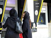 Iranian women use automated teller machines in Tehran in 2019