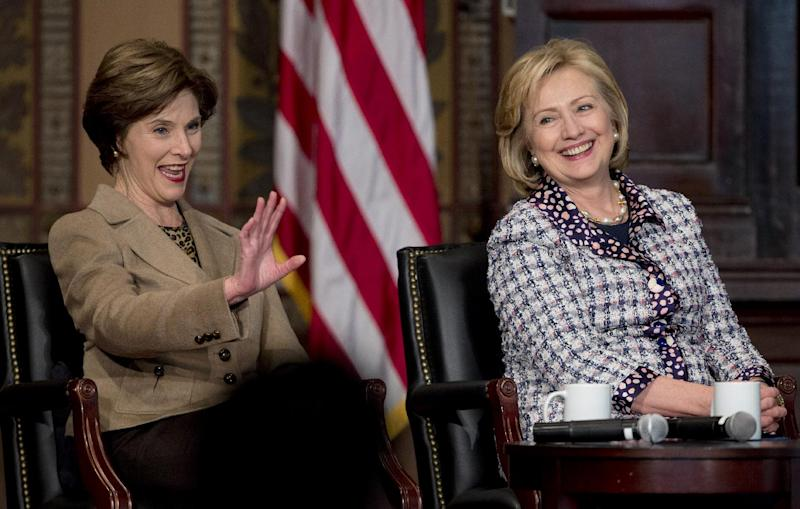 "Former first lady Laura Bush, left, and former Secretary of State Hillary Rodham Clinton, sit together on stage in Gaston Hall at Georgetown University in Washington, Friday, Nov. 15, 2013, during the ""Advance Afghan Women"" symposium. Secretary of State John Kerry and his predecessor, Clinton, say Afghanistan is reaching a turning point that will be critical to maintaining advances made by women since the end of Taliban rule. (AP Photo/Carolyn Kaster)"