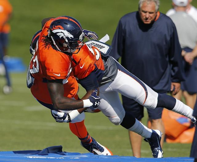 Denver Broncos' Danny Trevathan (59) is tackled by Lerentee McCray (55) during a drill at NFL football training camp on Tuesday, Aug 12, 2014, in Englewood, Colo. Trevathan was later injured and carted off the field. (AP Photo/Jack Dempsey)