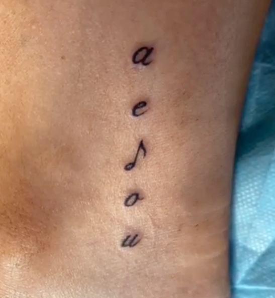 A close up of Carrie Bickmore's new ankle tattoo that features the letters a, e, o and u as well as a music note