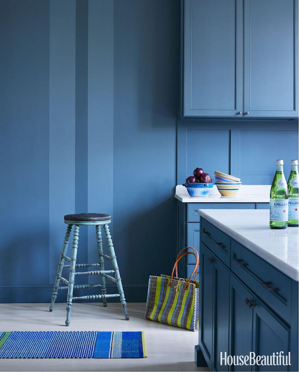 "<p>When the budget didn't allow for a <a href=""https://www.housebeautiful.com/home-remodeling/interior-designers/a3855/mary-douglas-drysdale-interview/"" rel=""nofollow noopener"" target=""_blank"" data-ylk=""slk:paneled kitchen"" class=""link rapid-noclick-resp"">paneled kitchen</a>, Mary Douglas Drysdale came up with another tactic for a cozy space: stripes. <a href=""https://www.sherwin-williams.com/"" rel=""nofollow noopener"" target=""_blank"" data-ylk=""slk:Sherwin-Williams"" class=""link rapid-noclick-resp"">Sherwin-Williams</a>'s Searching Blue coats the cabinets, while the walls use the same base color mixed 50 percent lighter and 150 percent darker.</p>"