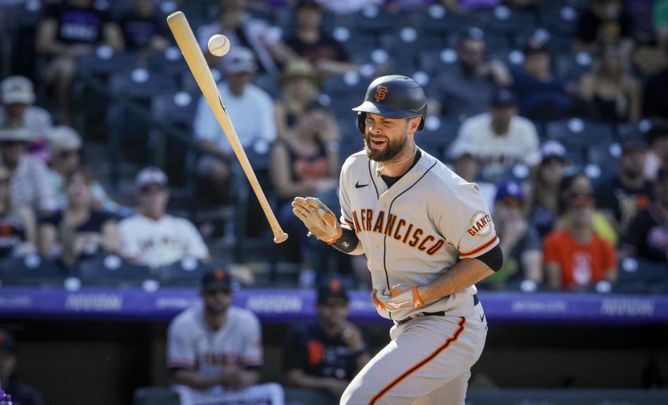 San Francisco Giants' Brandon Belt (9) is hit by a pitch from Colorado Rockies reliever Lucas Gilbreath in the seventh inning of a baseball game in Denver, Sunday, Sept. 26, 2021. (AP Photo/Joe Mahoney)