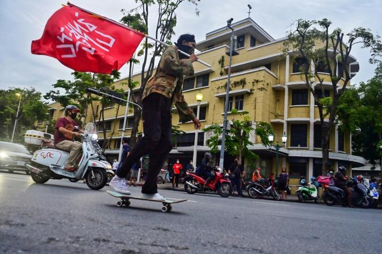 A skateboarder rides with a flag that reads, 'Prayut Get Out' during an anti-government protest in Bangkok (AFP/Lillian SUWANRUMPHA)