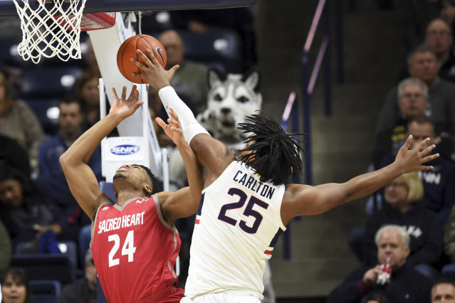 Connecticut's Josh Carlton (25) blocks a shot by Sacred Heart's E.J. Anosike (24) in the first half of an NCAA college basketball game, Friday, Nov. 8, 2019, in Storrs, Conn. (AP Photo/Stephen Dunn)