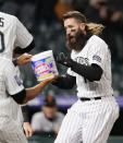 Colorado Rockies' Charlie Blackmon is welcomed by teammates at home plate affter Blackmon hit a three-run, walkoff home run of San Francisco Giants relief pitcher Camilo Doval in the seventh inning of game two of a baseball doubleheader Tuesday, May 4, 2021, in Denver. The Rockies won the nightcap by score of 8-6.(AP Photo/David Zalubowski)