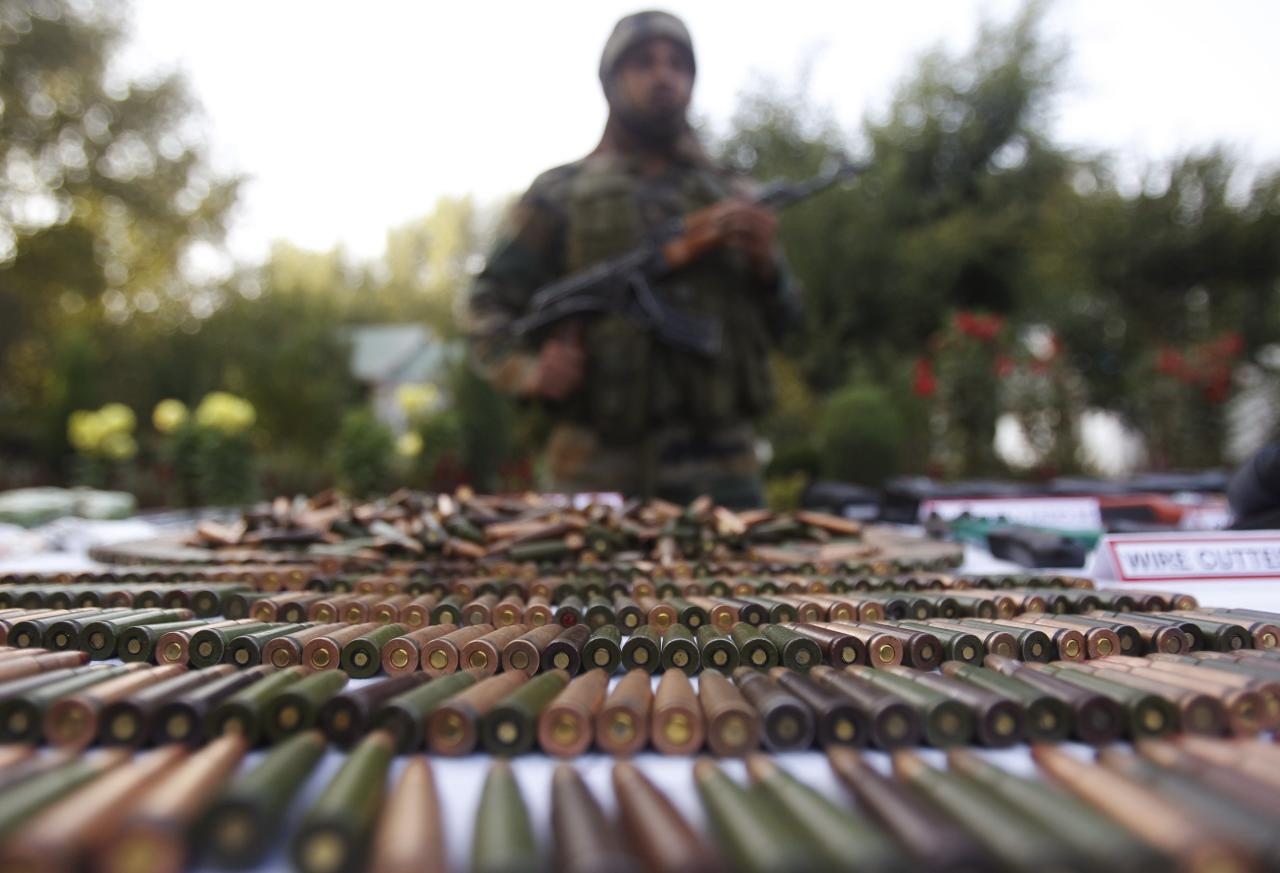 An Indian army soldier stands behind a display of seized arms and ammunition at a garrison in Srinagar, October 7, 2013. The Indian army on Monday displayed a cache of arms and ammunition, which according to them, were recovered from the Keran sector near the Line of Control (LoC) with Pakistan, on the 13th day of an operation. REUTERS/Danish Ismail (INDIAN-ADMINISTERD KASHMIR - Tags: MILITARY TPX IMAGES OF THE DAY)