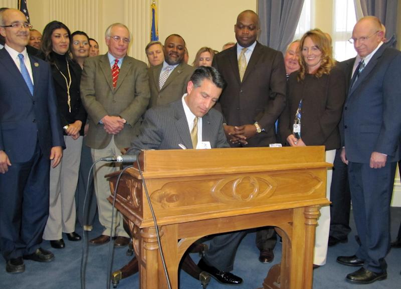 Gov. Brian Sandoval, surrounded by state lawmakers in the state's Old Assembly Chambers, signs AB114 legalizing online gambling in Nevada on Thursday, Feb. 21, 2013 in Carson City. (AP Photo/Sandra Chereb).