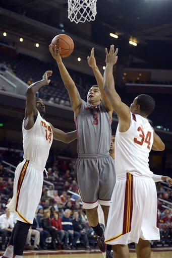 Washington State guard DaVonte Lacy, center, puts up a shot as Southern California forward Dewayne Dedmon, left, and forward Eric Wise defend during the first half of their NCAA college basketball game, Thursday, Feb. 7, 2013, in Los Angeles. (AP Photo/Mark J. Terrill)