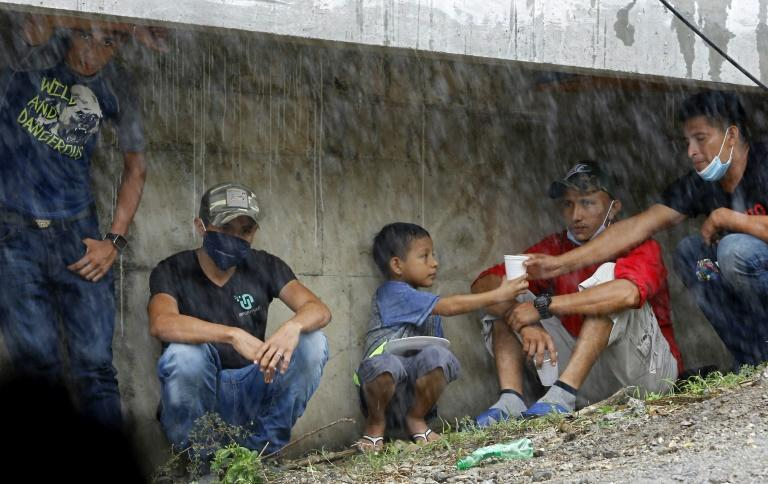 People take refuge under La Democracia bridge while waiting for relatives to be rescued from floods caused by the passage of Hurricane Iota in El Progreso, Yoro department, Honduras