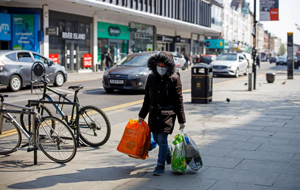 "A woman wearing a protective face mask carries bags of shopping down a street in Wood Green in north London on March 27, 2020, after Britain's government ordered a lockdown to slow the spread of the novel coronavirus COVID-19. - Britain is under lockdown, it's population joining around 1.7 billion people around the globe ordered to stay indoors to curb the ""accelerating"" spread of the coronavirus. (Photo by Tolga AKMEN / AFP) (Photo by TOLGA AKMEN/AFP via Getty Images)"