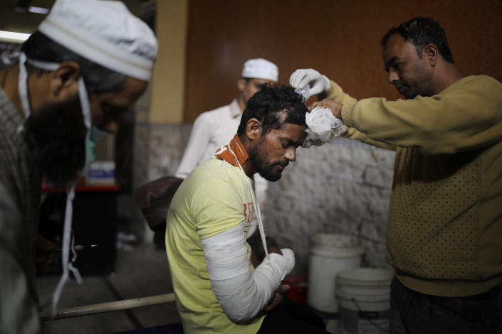 In this Friday, Feb. 28, 2020 photo, paramedics attend to the wounds of Mohammad Illyas at Al-Hind hospital in Old Mustafabad neighborhood of New Delhi, India. The hospital in the riot-torn neighborhood turned from a community clinic into a trauma ward, its doctors, for the first time, dealing with injuries like gunshot wounds, crushed skulls and torn male genitals. Authorities haven't said what sparked the violence that has left more than 40 dead and hundreds injured, but it was the culmination of growing tensions since the passage of a citizenship law in December that fast-tracks naturalization for some religious minorities from neighboring countries but not Muslims. (AP Photo/Altaf Qadri)