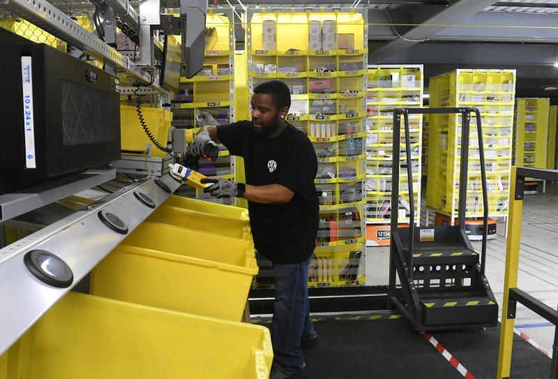 THORNTON, CO - FEBRUARY 19: Mike May pulls items out of pods to be delivered to customers at Amazon's Fulfillment Center on March 19, 2019 in Thornton, Colorado. The facility which opened in July of 2018 is 855,000 square feet, and employees over 1500 people. The Thornton facility is a state-of-the-art facility that uses Amazon Robotics to move the merchandise around from one area to the next. Hundreds of workers perform a variety of jobs in the huge facility. Many workers stand at stations, picking items to ship from trays brought to them by robots that roam the massive warehouse floor. The robotic facility, near I-25 and 144th Avenue, distributes small- and medium-sized items and allows for quicker delivery of orders in the metro area. (Photo by Helen H. Richardson/MediaNews Group/The Denver Post via Getty Images)
