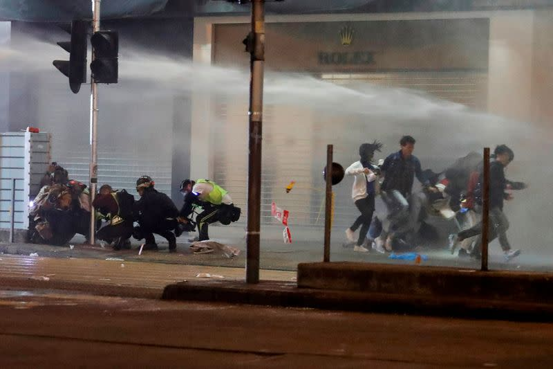 People run away from water cannon during a protest on New Year's Eve in Mongkok, Hong Kong