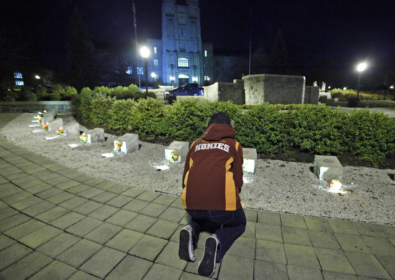 A student participates in an impromptu candlelight vigil in front of the 4/16 memorial on the campus of Virginia Tech after two shootings on the campus in Blacksburg, Va., Thursday, Dec. 8, 2011. A gunman killed a police officer and then apparently shot himself to death nearby in a baffling attack that shook up the campus nearly five years after it was the scene of the deadliest shooting rampage in modern U.S. history. (AP Photo/Steve Helber)