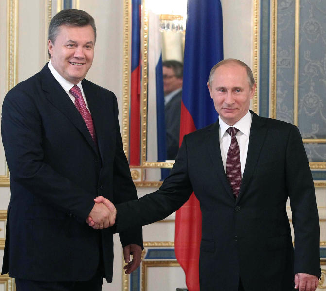 FILE - In this Saturday, July 27, 2013 file photo, Russian President Vladimir Putin, right, and his Ukrainian counterpart Viktor Yanukovych pose for photographers during their meeting in Kiev, Ukraine. More than 20 years after gaining independence from the Soviet Union and painfully searching for its place on the geopolitical map, Ukraine finally has a real chance to firmly align itself with the EU, with its democratic standards and free-market zone. The alternative is to slide back into Russia's shadow, both politically and economically. (AP Photo/RIA-Novosti, Mikhail Klimentyev, Presidential Press Service, File)