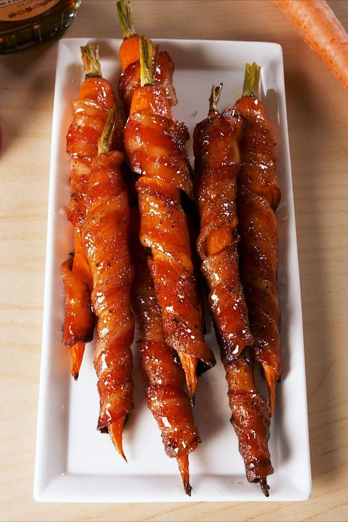 """<p>We'll take all our veggies wrapped in bacon, please.</p><p>Get the recipe from <a href=""""https://www.delish.com/cooking/a19625150/maple-bacon-carrots-recipe/"""" rel=""""nofollow noopener"""" target=""""_blank"""" data-ylk=""""slk:Delish"""" class=""""link rapid-noclick-resp"""">Delish</a>.</p><p><strong><a class=""""link rapid-noclick-resp"""" href=""""https://go.redirectingat.com?id=74968X1596630&url=https%3A%2F%2Fwww.barnesandnoble.com%2Fw%2Fdelish-editors-of-delish%2F1127659306%3Fst%3DAFF%26SID%3DBarnes%2B%2526%2BNoble%2B-%2BTop%2B100%253A%2BBook%2BBestsellers%262sid%3DSkimlinks_7689440_NA&sref=https%3A%2F%2Fwww.delish.com%2Fholiday-recipes%2Fchristmas%2Fg1421%2Fchristmas-side-dishes%2F"""" rel=""""nofollow noopener"""" target=""""_blank"""" data-ylk=""""slk:GET YOURS NOW"""">GET YOURS NOW</a><em> Delish Cookbook, </em><em>barnesandnoble.com</em></strong></p>"""