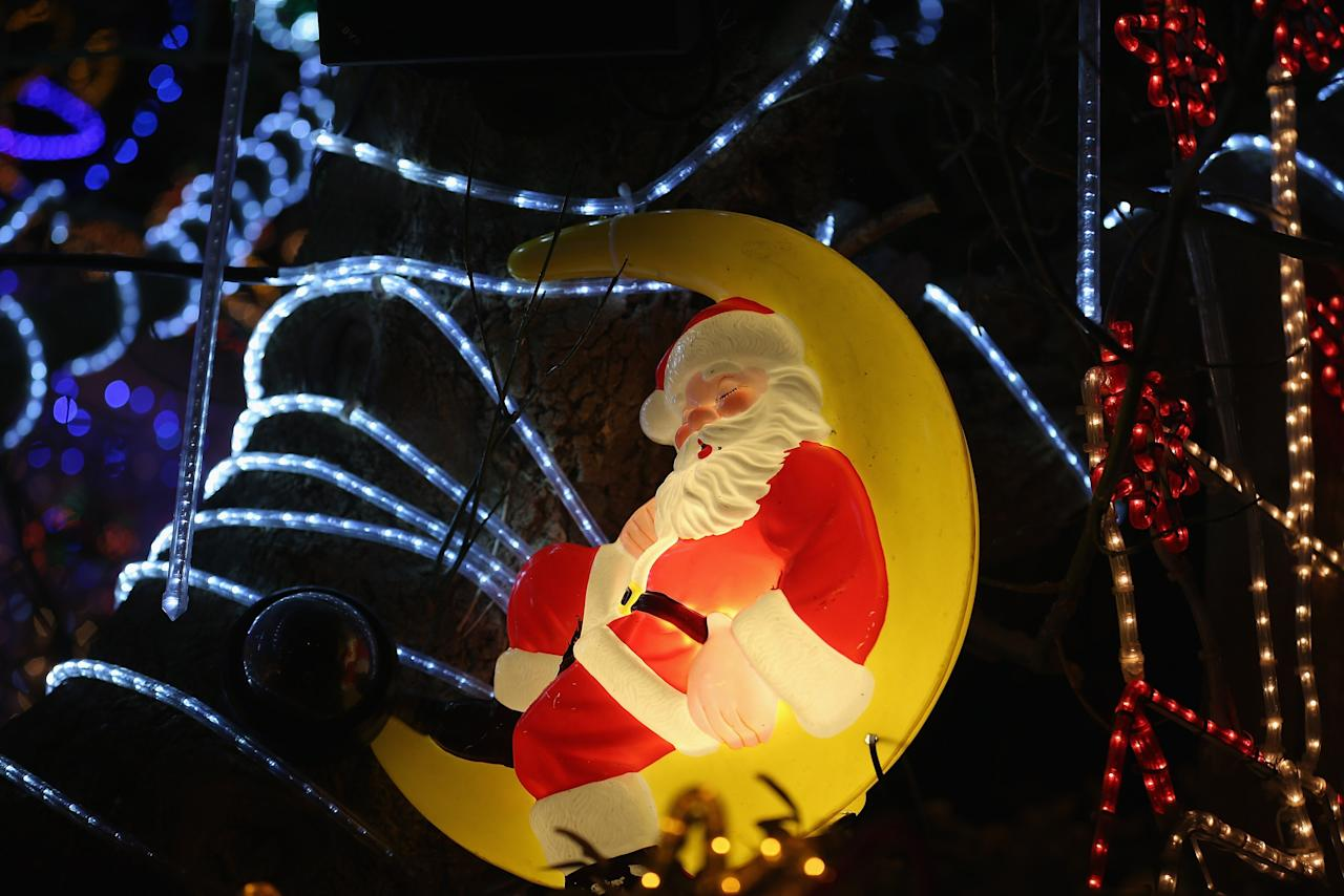 MELKSHAM, ENGLAND - DECEMBER 08:  Christmas festive lights adorn a detached house in a suburban street in Melksham, December 8, 2012 in Melksham, England. The lights, a popular festive attraction, have returned to the town after a two-year absence and have raised thousands of pounds for charity for a local hospice, Dorothy House.  The display, which is estimated to involve over 100,000 bulbs, worth over 30,000 GBP and even needed an up-rated electricity supply installed to cope with the additional power needed, is the brainchild of householder and electrician Alex Goodhind. This year, the display which Mr Goodhind began fifteen years ago now takes a team of professional electricians five weeks to complete, and even includes a snow machine.  (Photo by Matt Cardy/Getty Images)