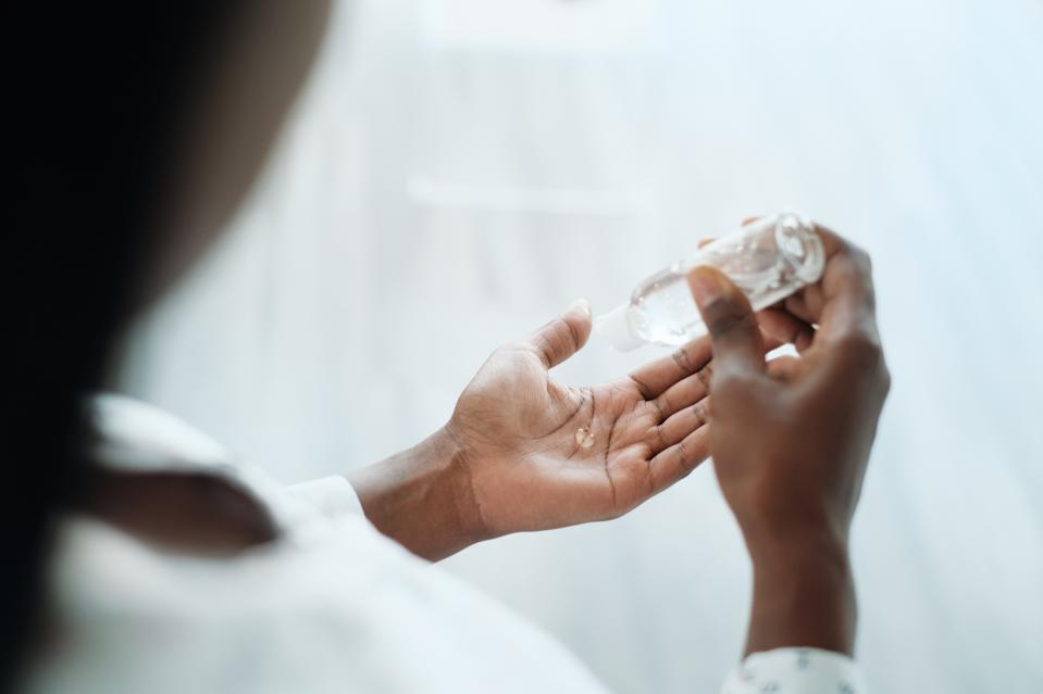 Back woman using liquid hand sanitizer. African american girl using alcohol-based gel to disinfect hand skin against virus, germs, bacteria for healthy lifestyle