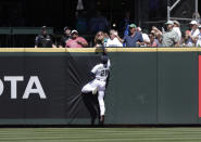 The home run ball hit by Colorado Rockies' Brendan Rodgers bounces among fans in the stands with Seattle Mariners center fielder Taylor Trammell leaping during the second inning of a baseball game, Wednesday, June 23, 2021, in Seattle. (AP Photo/John Froschauer)