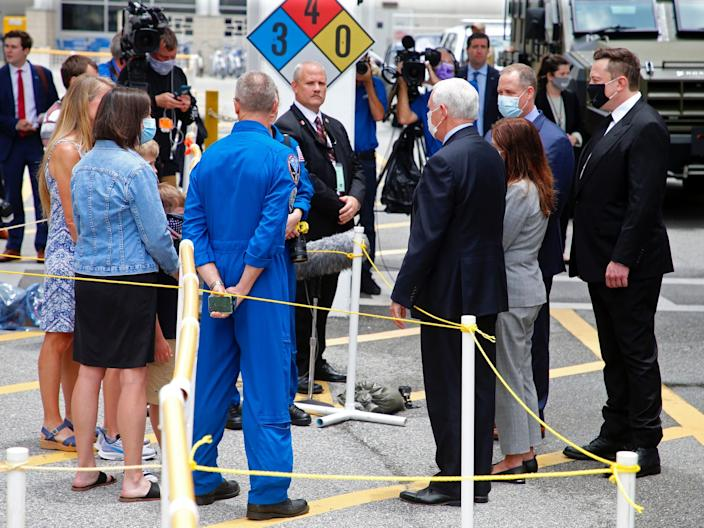 Elon Musk (right), Vice President Mike Pence, NASA Administrator Jim Bridenstine, and the families of astronauts Bob Behnken and Doug Hurley (left) talk ahead of the first scheduled launch at the Kennedy Space Center, in Cape Canaveral, Florida, May 27, 2020.