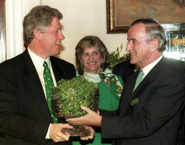 (FILES) In this file photo taken on March 17, 1993, US President Bill Clinton (L), with Jean Kennedy Smith (C), accepts a bowl of shamrocks in honor of St. Patrick's Day from Irish Prime Minister Albert Reynolds during a meeting in the White House in Washington, DC (AFP Photo/Paul J. RICHARDS)
