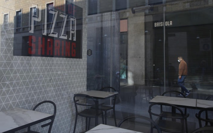 A man walks past a closed restaurant pizzeria in Milan, Italy, Saturday, April 24, 2021. Italy plans to start emerging from rolling partial lockdowns that were imposed during a fall virus surge, reopening outdoor dining and schools at all grade levels in lower-risk regions starting April 26. (AP Photo/Antonio Calanni)