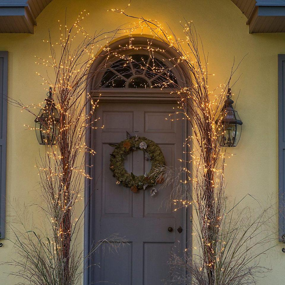 <p>If you don't want to go all-out on holiday decor, you can opt for a simpler, more natural holiday look. Add small lights to some tall branches to frame your door—this style will last throughout the whole winter season.</p>