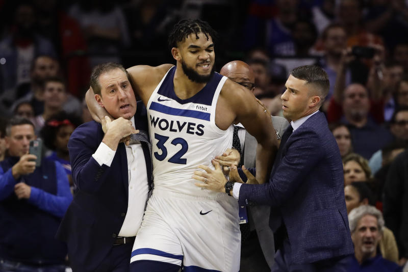 Minnesota Timberwolves' Karl-Anthony Towns is led away after an altercation with Philadelphia 76ers' Joel Embiid during the second half of an NBA basketball game Wednesday, Oct. 30, 2019, in Philadelphia. Both players were ejected. The 76ers won 117-95. (AP Photo/Matt Rourke)