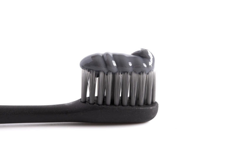 Black Toothbrush with Black Activated Charcoal Toothpaste on a White Background